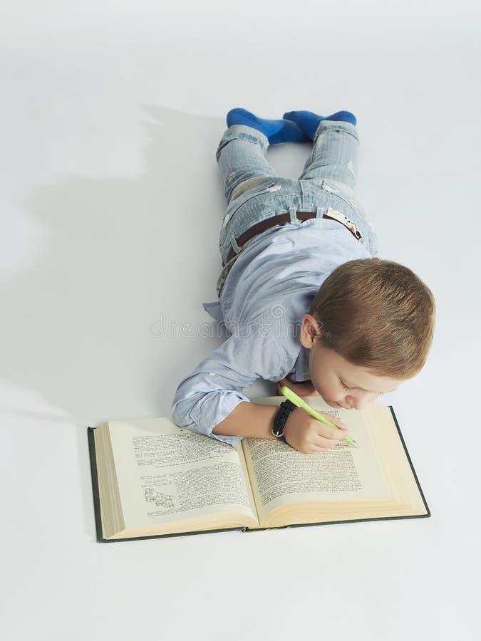 有书的小男孩在地板上 滑稽的儿童作家 免版税库存图片