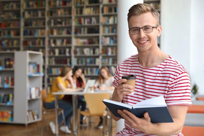 有书的年轻人和饮料在图书馆里 库存照片