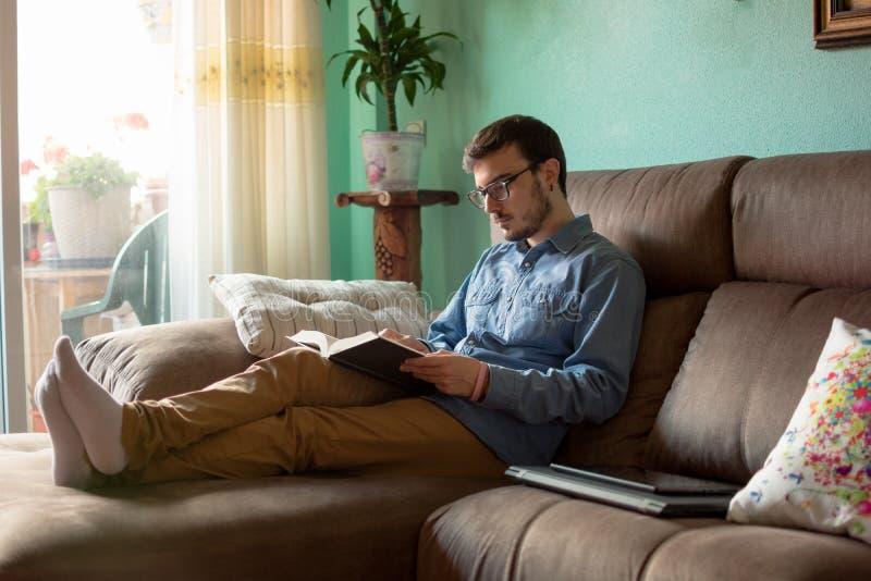 有书的年轻人在沙发在家 免版税库存照片