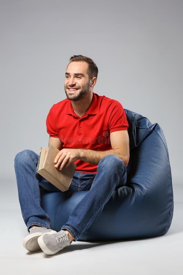 有书的年轻人坐装豆子小布袋椅子反对灰色背景 免版税库存图片