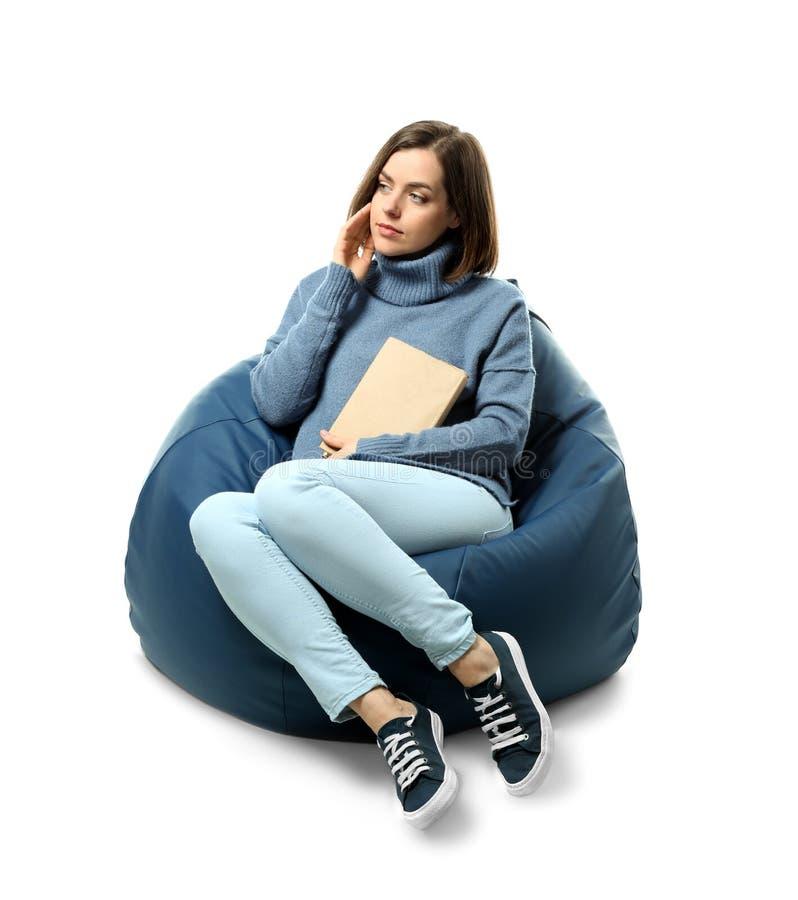 有书的年轻女人坐装豆子小布袋椅子反对白色背景 图库摄影