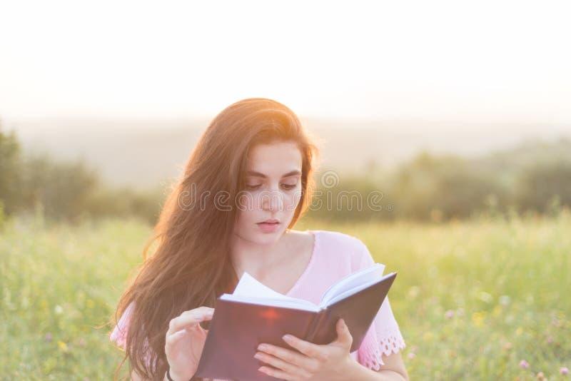 有书的年轻美丽的女孩在自然 库存照片