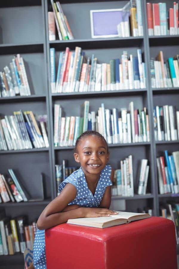 有书的微笑的女孩在无背长椅在图书馆里 库存照片