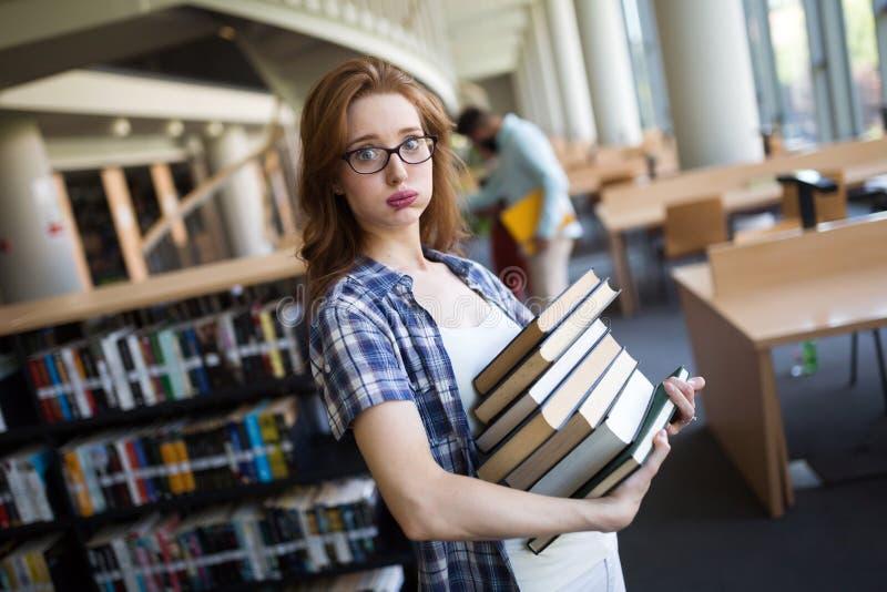 有书的沮丧的青少年的学生女孩 免版税库存照片