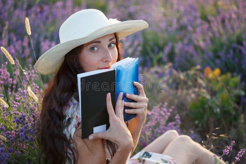 有书的浪漫妇女在淡紫色领域 库存图片