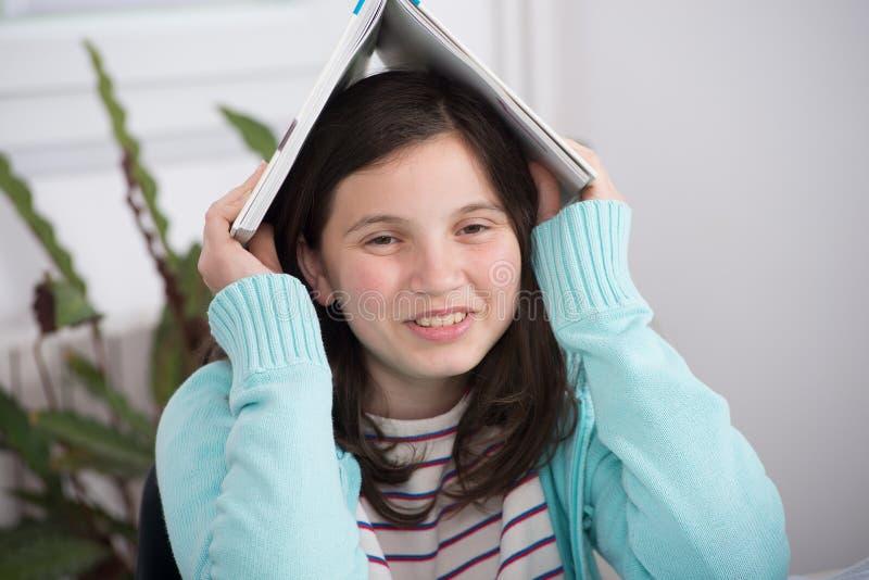 有书的滑稽的十几岁的女孩在她的头 库存图片