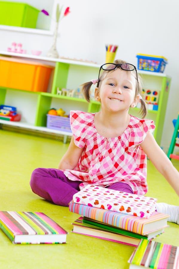 有书的滑稽的小女孩在楼层上 免版税库存照片