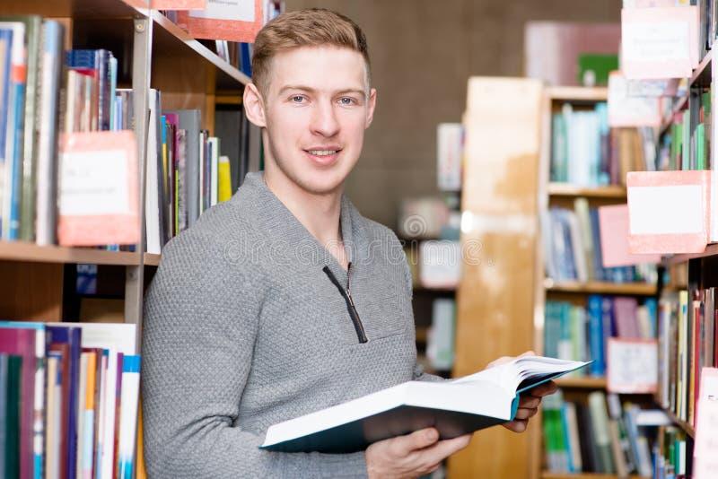 有书的男学生在看照相机的图书馆里 库存图片