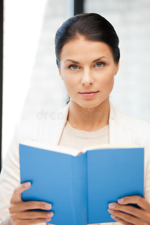 有书的镇静和严肃的妇女 免版税库存图片