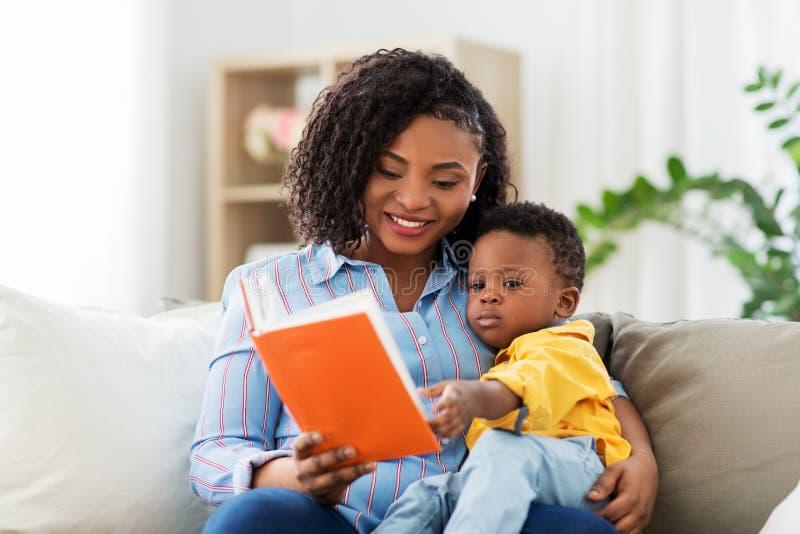 有书的非裔美国人的母亲和婴孩在家 免版税库存照片