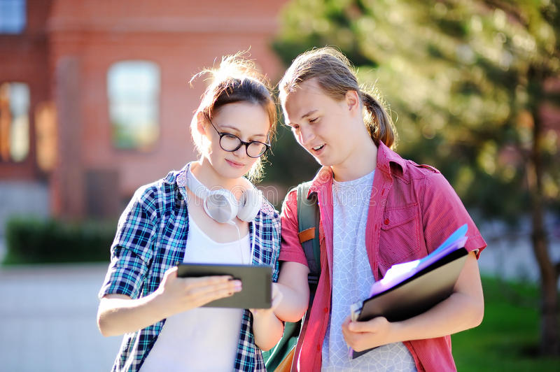 有书的年轻愉快的学生和笔记在大学里 免版税图库摄影