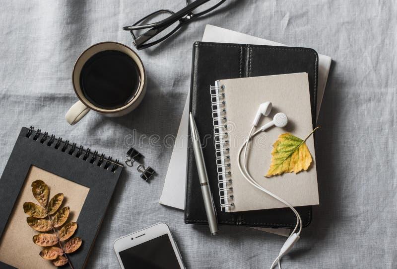 有事务的家庭工作场所,教育,教育辅助部件 笔记薄,片剂,电话, earbuds,笔,玻璃,在灰色ba的咖啡 库存图片