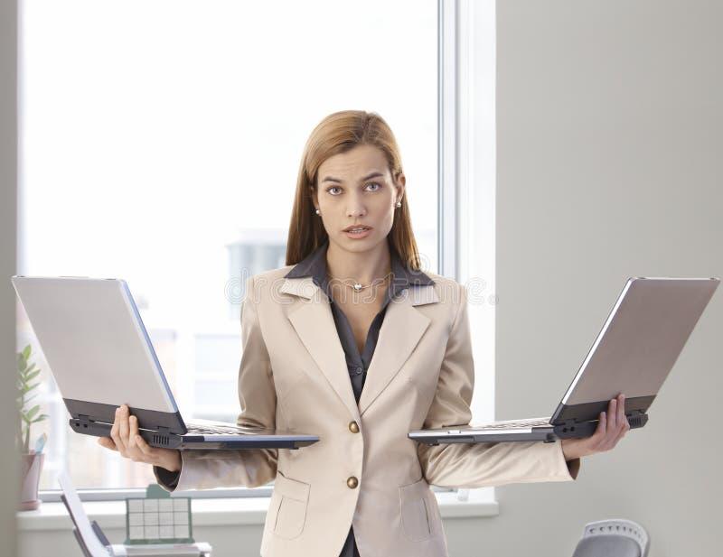 有二台膝上型计算机的绝望女实业家 免版税库存照片