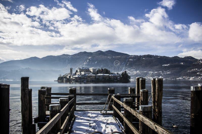 有云彩和金黄水的意大利湖 小木码头,您能看到太阳的光芒在水的 免版税库存照片
