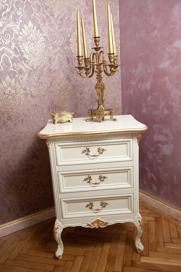 有五个蜡烛的金黄烛台在豪华织地不很细墙壁前面的白色木家具 库存图片