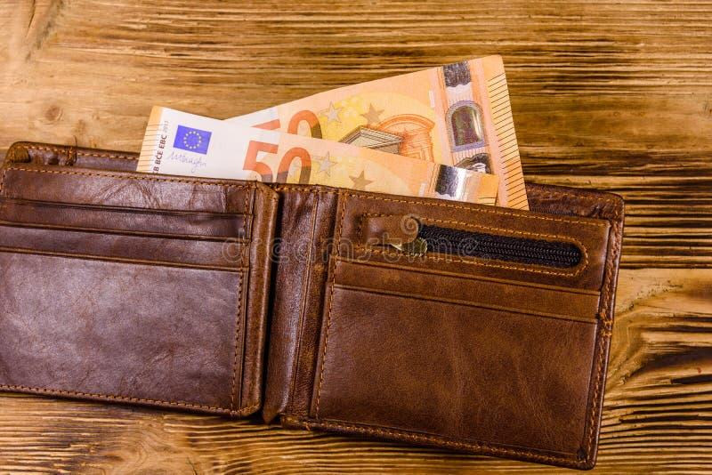 有五十张欧元钞票的布朗皮革钱包在木背景 r 库存照片