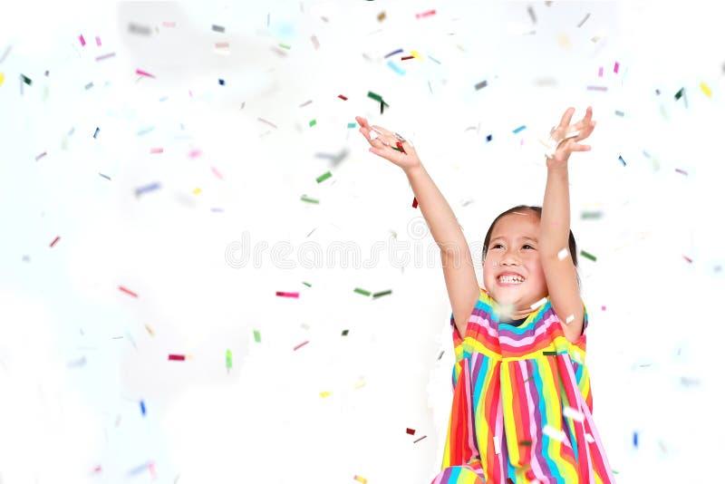 有五颜六色的五彩纸屑的愉快的小孩女孩在白色背景 新年快乐或祝贺概念 库存照片