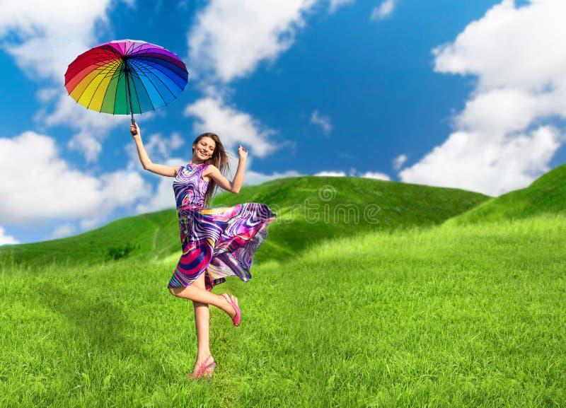 有五颜六色的伞的俏丽的微笑的妇女 库存照片