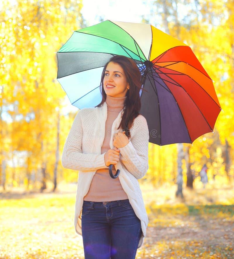 有五颜六色的伞的愉快的微笑的妇女在温暖的晴朗的秋天 库存照片