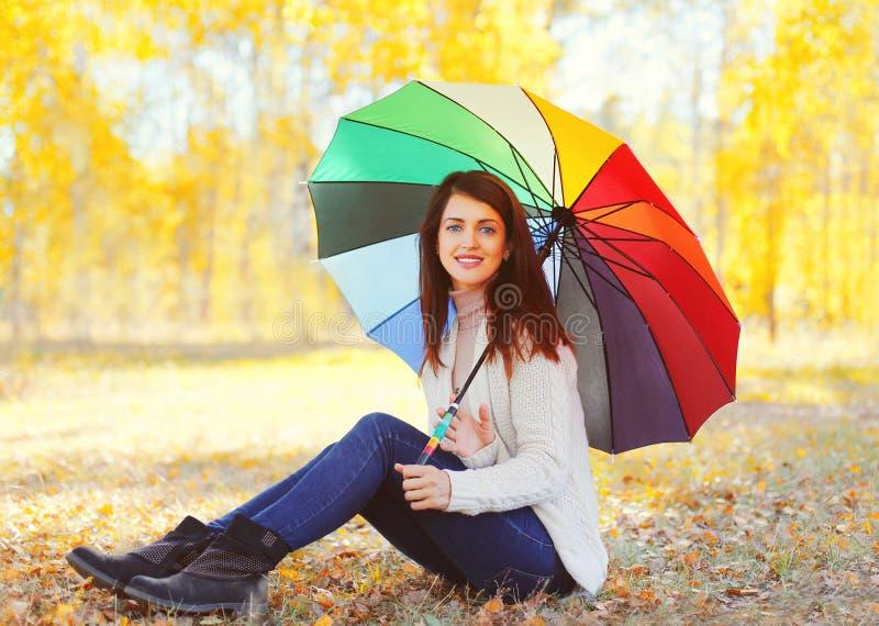 有五颜六色的伞的愉快的美丽的微笑的妇女在温暖的晴朗的秋天 免版税库存照片