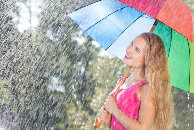 有五颜六色的伞的白肤金发的妇女 库存照片
