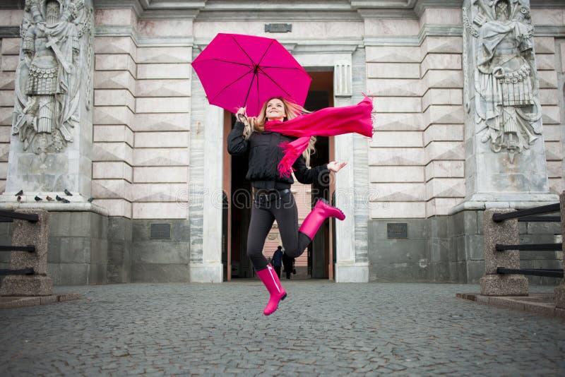 有五颜六色的伞的美丽的年轻和愉快的白肤金发的妇女在街道上 阳和乐观的概念 图库摄影