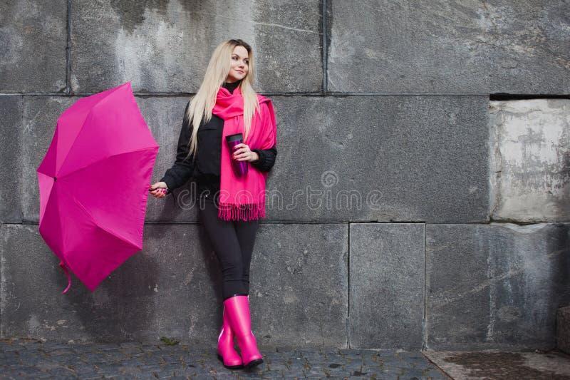 有五颜六色的伞的美丽的年轻和愉快的白肤金发的妇女在街道上 阳和乐观的概念 免版税库存照片