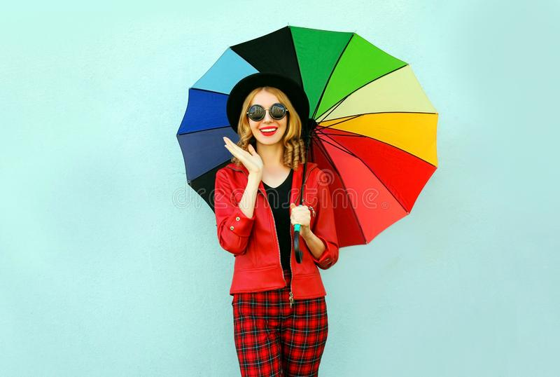 有五颜六色的伞的,佩带的红色夹克,在蓝色墙壁上的黑帽会议愉快的年轻惊奇的妇女 库存照片