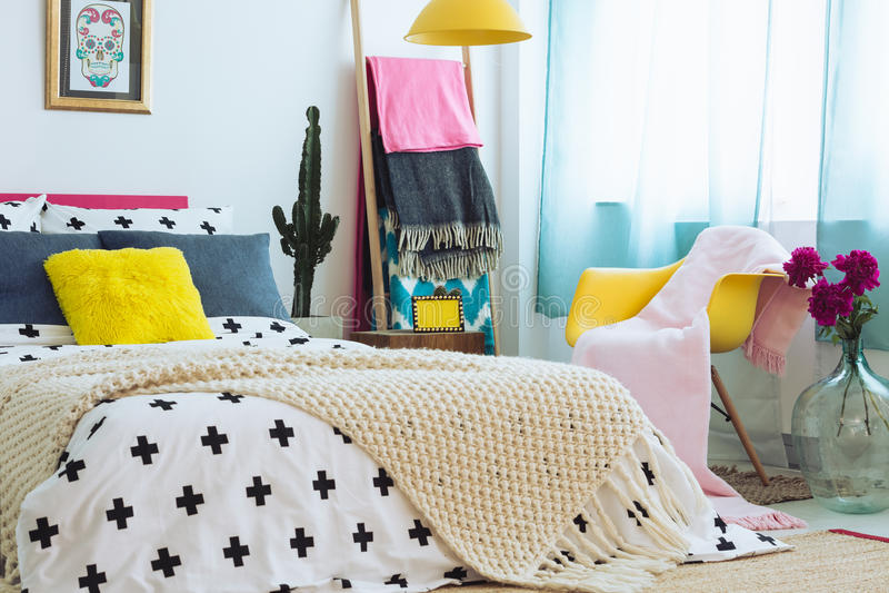 有五颜六色的卧具的时髦卧室 库存照片