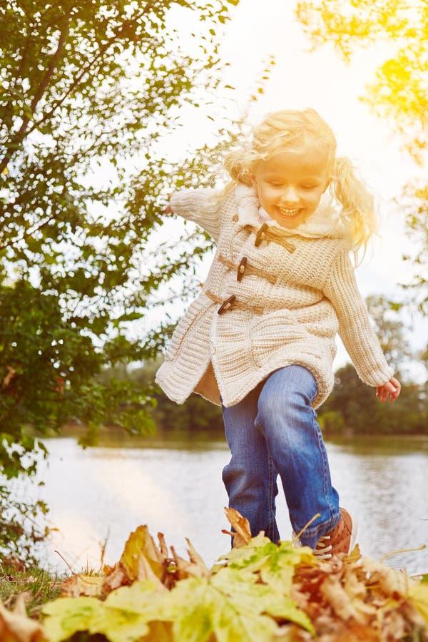 有五颜六色的叶子的愉快的女孩 图库摄影