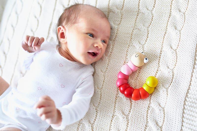 有五颜六色的木玩具的新出生的女婴 库存图片
