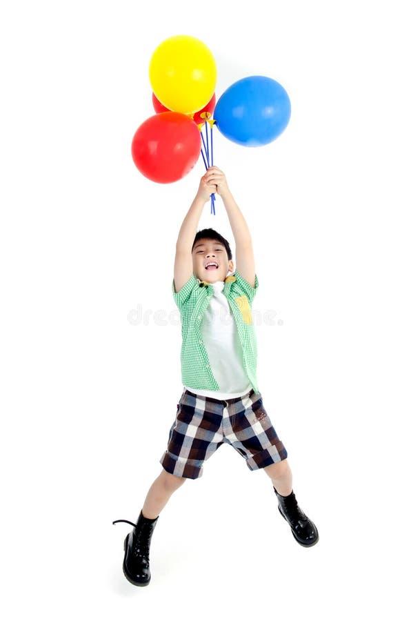 有五颜六色的气球的愉快的亚裔逗人喜爱的男孩 免版税库存图片