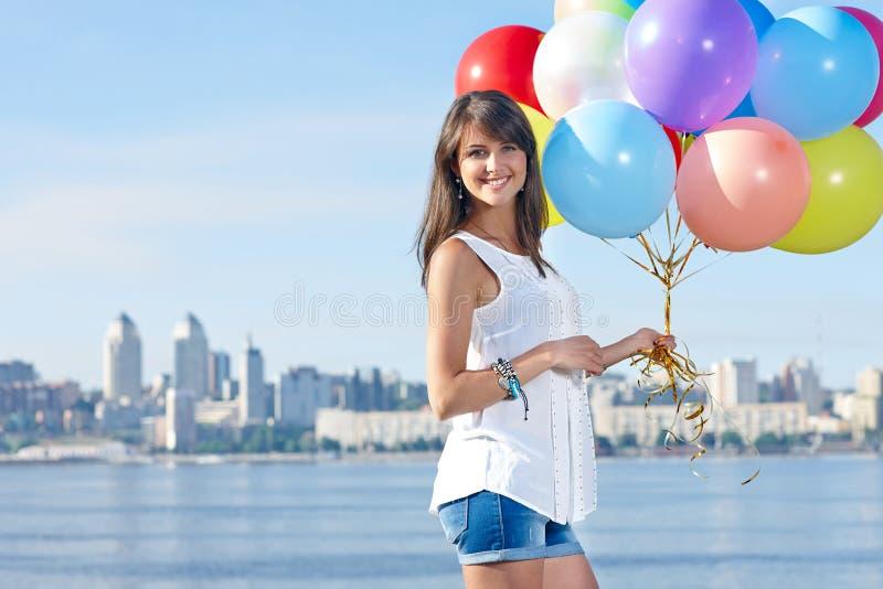有五颜六色的气球的愉快的少妇 库存图片