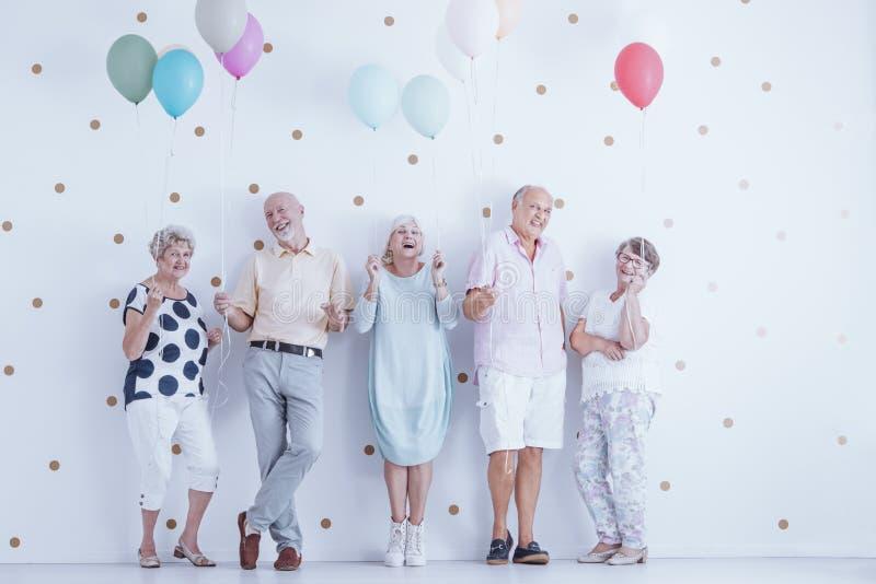 有五颜六色的气球的愉快的资深人庆祝朋友` s生日的 库存照片