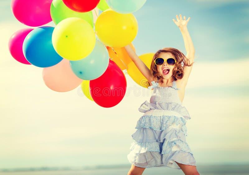 有五颜六色的气球的愉快的跳跃的女孩 图库摄影