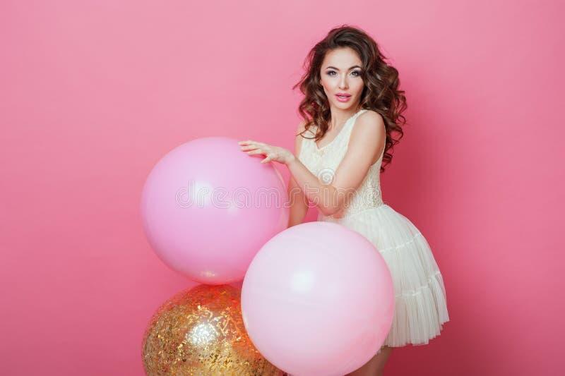 有五颜六色的气球的秀丽女孩笑在桃红色背景的 生日节日晚会的美丽的愉快的少妇 Fashi 免版税库存照片
