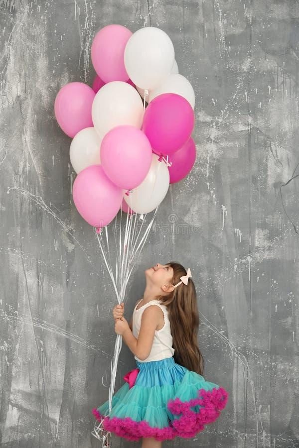 有五颜六色的气球的逗人喜爱的生日女孩临近难看的东西墙壁 库存图片