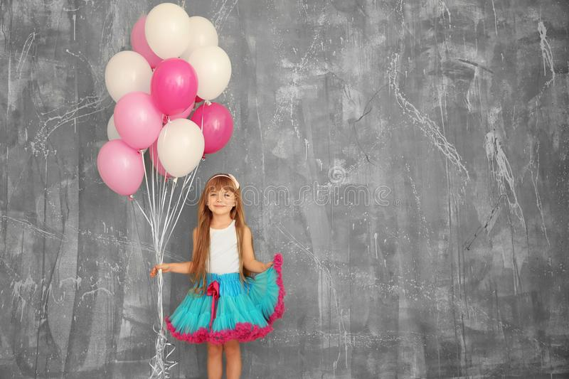 有五颜六色的气球的逗人喜爱的生日女孩 免版税库存照片