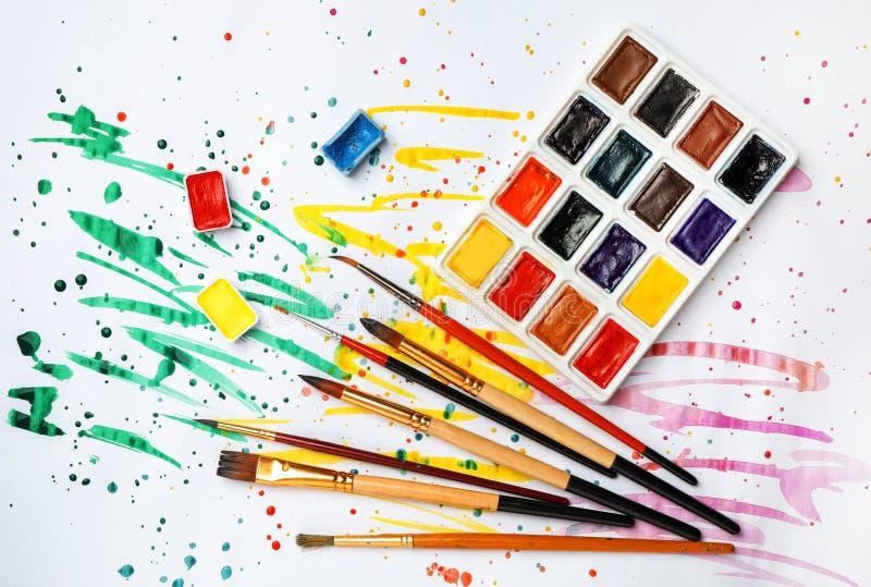 有五颜六色的油漆和刷子的塑料调色板 免版税库存图片