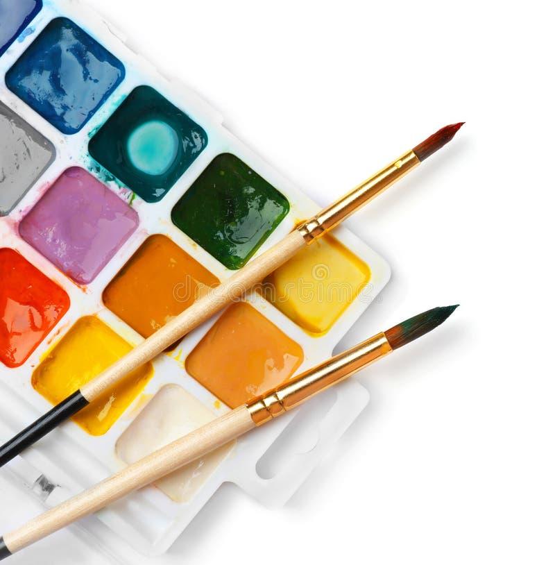 有五颜六色的油漆和刷子的塑料调色板 图库摄影