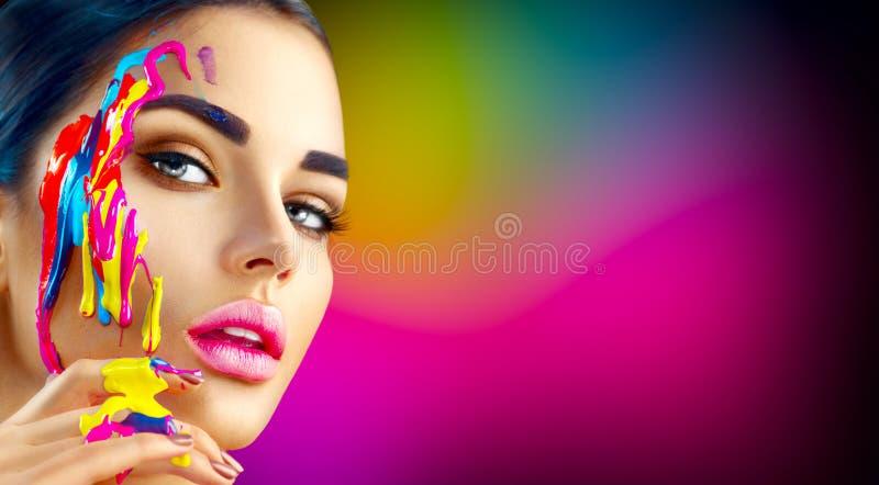 有五颜六色的油漆的秀丽式样女孩在她的面孔 美丽的妇女画象有流动的油漆的 库存照片