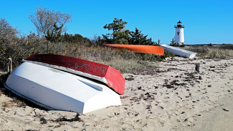 有五颜六色的渔船的新英格兰灯塔在岸 免版税库存照片