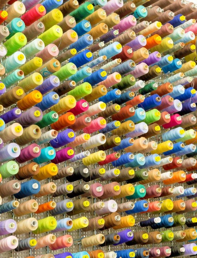 有五颜六色的缝合针线的短管轴 免版税库存照片