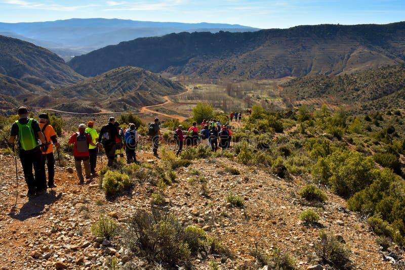 有五颜六色的背包的成人人迁徙在沙子和石头道路步行沿着向下与惊奇的一座山的小组  库存照片