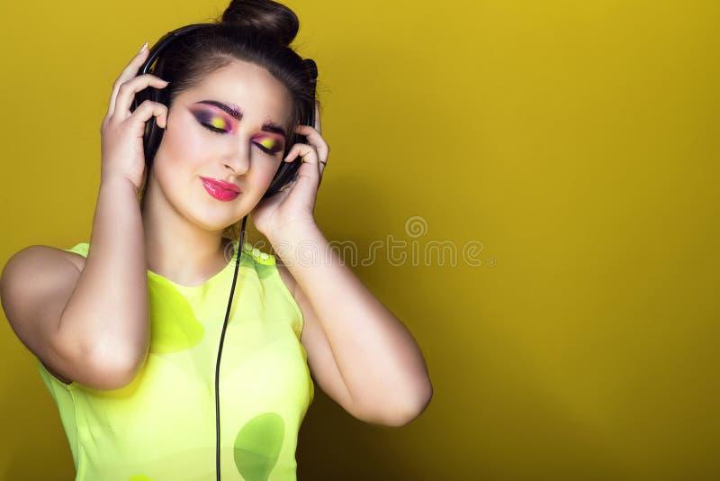 有五颜六色的艺术性的构成和updo头发的听到在耳机和微笑的音乐的年轻俏丽的女孩画象  免版税库存图片