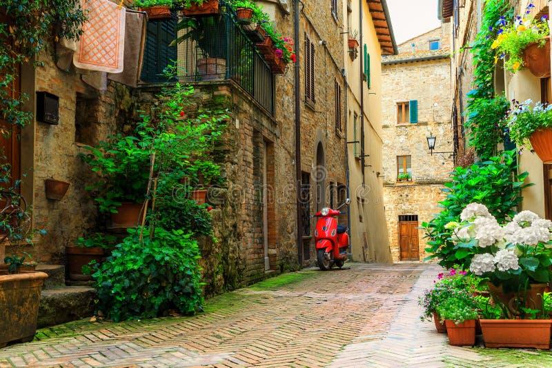 有五颜六色的花和滑行车的,皮恩扎,托斯卡纳典型的意大利街道 免版税库存图片