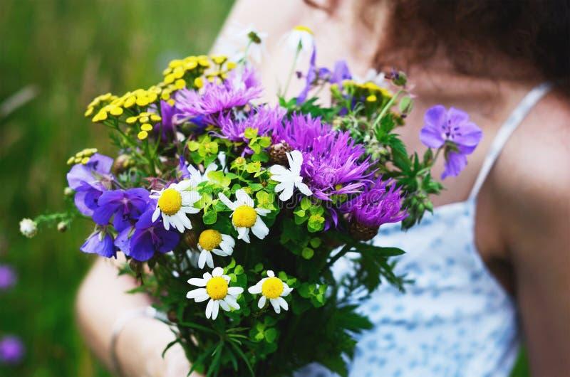有五颜六色的花花束的女孩在夏天领域的 库存图片