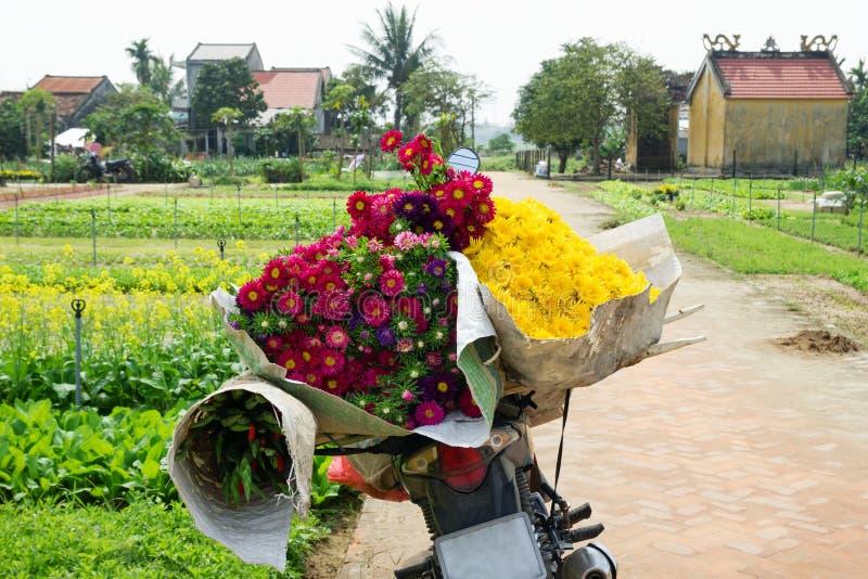 有五颜六色的花花束的摩托车在一条农村路的 库存图片