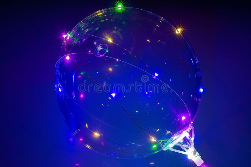 有五颜六色的被带领的光的美丽的气球在蓝色背景 党/假日背景 免版税库存图片