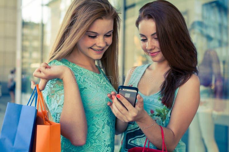 有五颜六色的购物袋和手机的两个美丽的女孩 库存图片